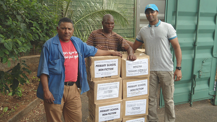 3 African men with a stack of boxed books. All three men leaning on the stack of boxes.