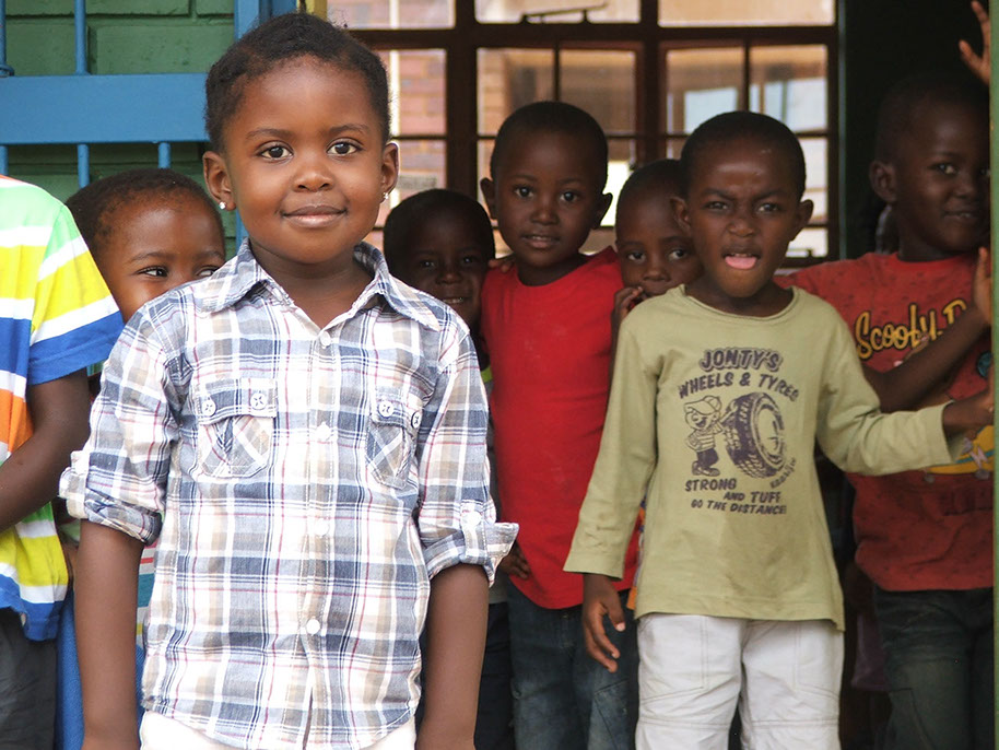 African children smiling at camera, two in the foreground, several in the background. Setting is probably outside a classroom.