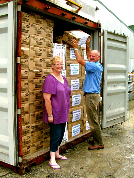 Two white skinned people, Linda Abblitt and Rodney Ziersch putting the final box into a shipping container, the container is completely full of boxes.